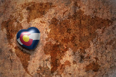 Heart with colorado state flag on a vintage world map crack paper background. Concept stock images