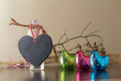 Heart with colorful Easter chickens. Blank black heart hanging on a glass bottle alongside colorful Easter chickens and an artistic twig with copyspace for your Stock Image
