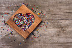 Heart from colourful beads in wooden heart-shaped box Royalty Free Stock Photos