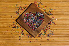 Heart from colourful beads in wooden heart-shaped box Stock Photography