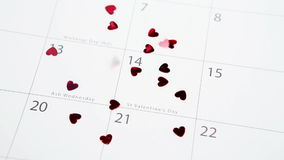 Heart confetti falling on calendar on highlighting valentines day. Focus shot stock video footage