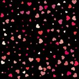 Heart confetti of Valentines petals falling on black background. Flower petal in shape of heart confetti for Women's Day Stock Photo