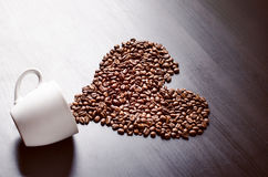 Heart consist from coffee beans. Coffee roasted beans on a shape like a heart and coffee cup. Rustic background. Energy. Royalty Free Stock Photo