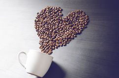 Heart consist from coffee beans. Coffee roasted beans on a shape like a heart and coffee cup. Rustic background. Energy. Royalty Free Stock Image