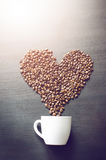 Heart consist from coffee beans. Coffee roasted beans on a shape like a heart and coffee cup. Rustic background. Energy. stock photography