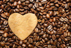 Heart cookie on coffee beans background. Heart shaped smiling cookie on roasted coffee beans background Stock Image