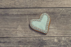 Heart cookie covered with blue icing and edible pearl beads Stock Images