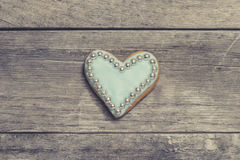 Heart cookie covered with blue icing and edible pearl beads Stock Photos