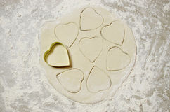 A heart cookie cutter on dough with shapes Stock Images