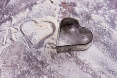 Heart from a cookie cutter in flour Royalty Free Stock Images
