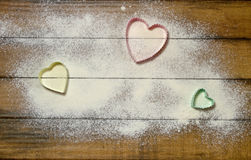 Heart Cookie Cutters on Floured Wood Stock Photo
