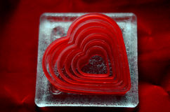 Heart cookie cutters on glass coaster against red velvet background Royalty Free Stock Photography