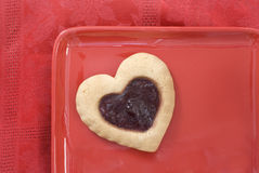 Heart Cookie on Red Plate. Cherry filled heart cookie on a red plate against a red tablecloth Royalty Free Stock Photos