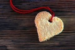 Heart cookie with red ribbon on dark old wood, copy space Stock Images