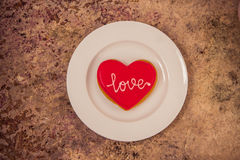 Heart cookie on a white plate with text Love on it Royalty Free Stock Images