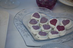 Heart Cookies. Cookies and cream dipped in white chocolate and topped with hearts on a heart plate with white tablecloth Stock Photo