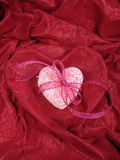 Heart cookies in heart fabric. Stack of heart sugar cookies tied with ribbon and placed in red heart shaped fabric Stock Photo