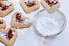 Heart cookies with strainer sugar on baking paper Royalty Free Stock Photography