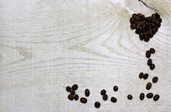 Heart and corner frame border of coffee beans on light wooden background. Royalty Free Stock Photos