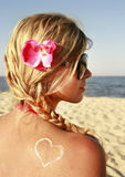 Heart of the cream on the female back on the beach Royalty Free Stock Photos