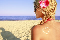 Heart of the cream on the female back on the beach. A heart of the cream on the female back on the beach Stock Photo