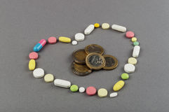 Heart created from colored pills with money. Medical concept Royalty Free Stock Photography