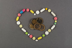 Heart created from colored pills with money. Medical concept Stock Photography
