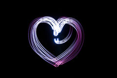 Heart created by light over black background Stock Photography