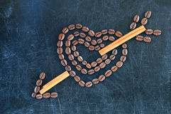 Heart with cupid arrow made of coffee beans on a dark background. Stock Image