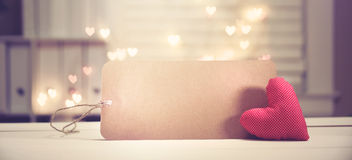 Heart cushion with card. On heart shaped light background stock images