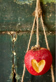 Heart cut into red apple hanging from string. Over old weathered dark background with copy space stock images