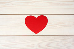 Heart cut from red paper. Heart symbol cut out of red paper on a wood background Stock Photography