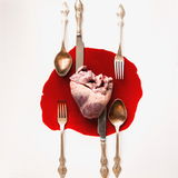 Heart and cutlery in a blood pool. On a white background Stock Images