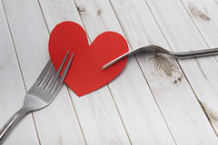 Heart and cutlery on a wooden background, bright boards, Valentine`s Day stock image