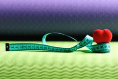 Heart decoration and flexible ruler lying on yoga mat. Measuring tape roll in cyan color and soft red heart on green and purple background. Workout and sport royalty free stock photos