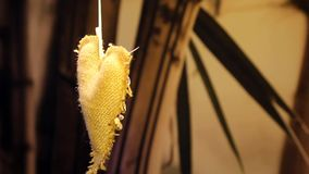 Heart decoration. Hanging decoration in form of heart. It is made of burlap and decorated with beads and ribbons. On the background a bamboo branch and leaves stock footage
