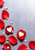 Heart decoration on red rose petals. Romance concept. Flat lay, top view. White heart decoration on red rose petals background on grey table. Romance concept Royalty Free Stock Photos