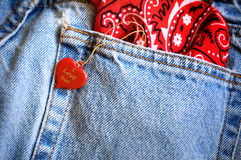 Heart and denim jeans. A red bandanna sticks out of the back pocket of a person wearing denim blue jeans.  A heart dangles on a gold cord from the pocket with I Royalty Free Stock Image