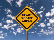 Heart disease ahead. Text 'heart disease ahead' inscribed on yellow highway style sign in black uppercase letters, background of blue sky and cloud stock photos