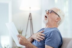 Shocked senior man having heart attack stock image