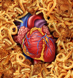 Heart Disease Food. Medical health care concept with a human heart organ surrounded by groups of greasy cholesterol rich fried foods as a symbol of arteries Stock Image