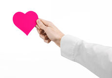 Heart Disease and Health Topic: hand doctor in a white shirt holding a card in the form of a pink heart isolated Royalty Free Stock Photo