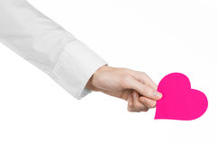 Heart Disease and Health Topic: hand doctor in a white shirt holding a card in the form of a pink heart isolated Stock Photos