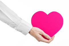 Heart Disease and Health Topic: hand doctor in a white shirt holding a card in the form of a pink heart isolated Stock Image