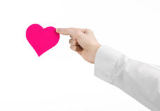 Heart Disease and Health Topic: hand doctor in a white shirt holding a card in the form of a pink heart isolated Royalty Free Stock Photography