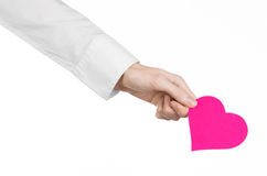 Heart Disease and Health Topic: hand doctor in a white shirt holding a card in the form of a pink heart isolated Stock Photo