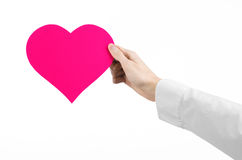 Heart Disease and Health Topic: hand doctor in a white shirt holding a card in the form of a pink heart isolated Royalty Free Stock Images