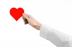 Heart Disease and Health Topic: hand doctor in a white shirt holding a card in the form of a red heart isolated Royalty Free Stock Photography