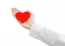 Heart Disease and Health Topic: hand doctor in a white shirt holding a card in the form of a red heart isolated Royalty Free Stock Photos