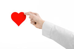 Heart Disease and Health Topic: hand doctor in a white shirt holding a card in the form of a red heart isolated Stock Image